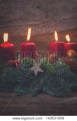 Evergreen fir tree advent garland with burning candles on wooden background, retro toned