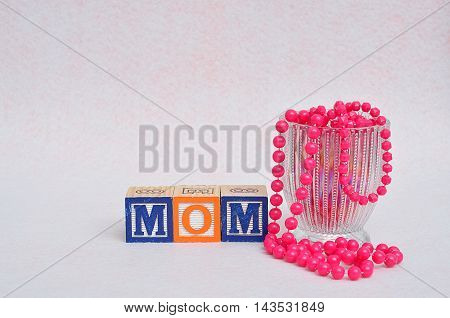 Mom spelled with block displayed with a glass filled with pink beads