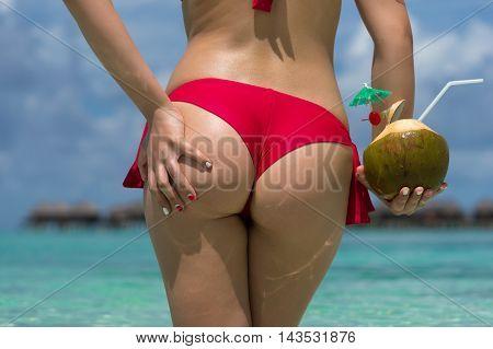 Close Up Girl Back In Bikini Against Ocean Beach And Coconut