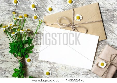Blank greeting card and envelope with white chamomile flowers and vintage gift box on white rustic wood background for creative work design
