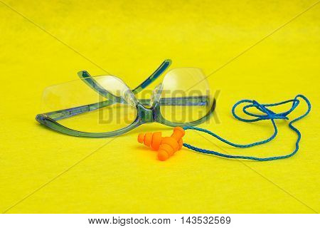 Safety goggles and ear plugs isolated on a yellow background