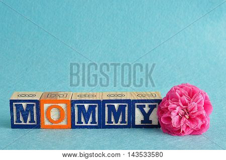 The word mommy spelled with alphabet blocks against a blue background with a pink flower