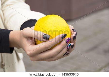 In the hands of a girl with a stylish manicure Orange bright orange