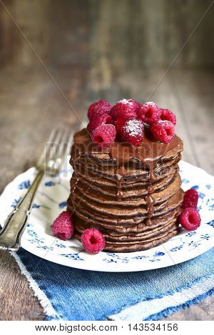 Stack Of Chocolate Pancakes Topped With Chocolate And Fresh Raspberry.