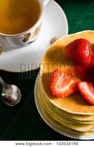 Traditional breakfast: pancakes with syrup and strawberry green tea. Still life served on green wooden table.