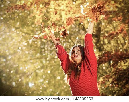 Happiness carefree. woman relaxing in autumn park throwing leaves up in the air with arms raised up. Beautiful girl in colorful forest foliage outdoor.