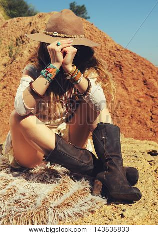 Traveller fashion woman sitting on a fur on rock, no face, outdoor, safari travel concept
