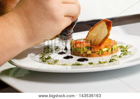Professional chef decorate Salmon with Avocado Tartare with Lemon Slice isolated on white