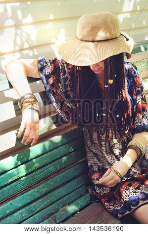 Pretty young woman with dreadlocks dressed in indie boho style, resting outdoor