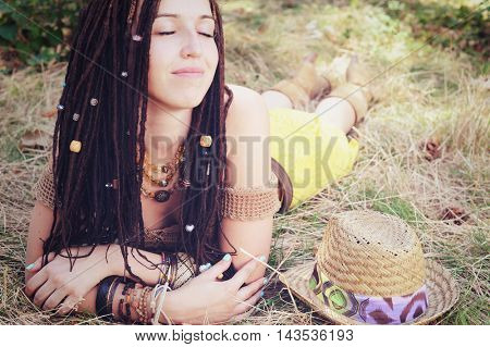 Relaxed and calm indie style woman with dreadlocks hairstyle, lying with closed eyes resting on the dry grass, outdoor