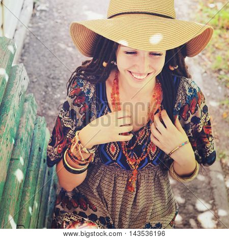 Joyful young woman portrait with dreadlocks dressed in boho style dress and necklace, sunny outdoor, vintage colors