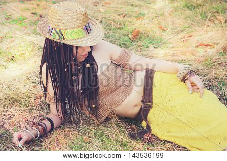 Fashion outdoor woman portrait with dreadlocks, dressed in knitted top, yellow skirt and straw hat, resting on the dry grass in park. Boho, indie, hippie style