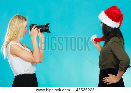 Photographer and model. Caucasian blonde girl shooting images taking photos with camera. photographing african woman in santa helper hat.