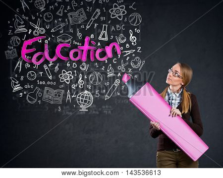 Schoolgirl with big marker writing on the wall word education