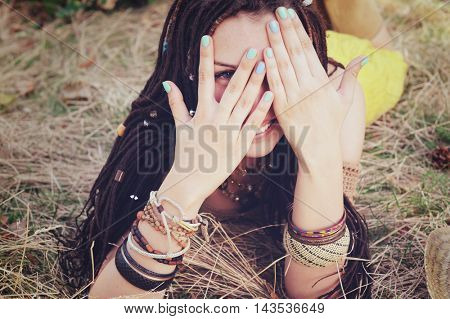 Joyful indie style woman with dreadlocks hairstyle, have a fun closing her face with a hands, sunny summer outdoor, vintage colors