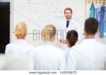 Young university professor studying students in front of blackboard