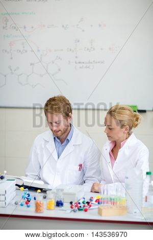 Couple of young chemists prepare lecture in chemical cabinet