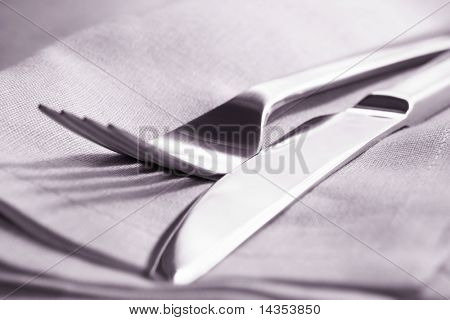 Knife and fork on napkin.  Close-up view, with shallow depth of field.  Toned image.