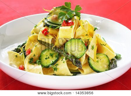 Fresh pappardelle with zucchini, asparagus, peppers, and a creamy sauce.  Delicious wide ribbon pasta, garnished with parsley and lemon zest.