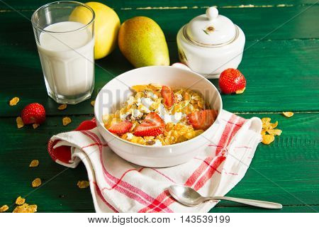 Breakfast of oatmeal and corn flakes with milk and strawberries. Still life in a rustic style with a view of the top of the breakfast laid on a green wooden table.
