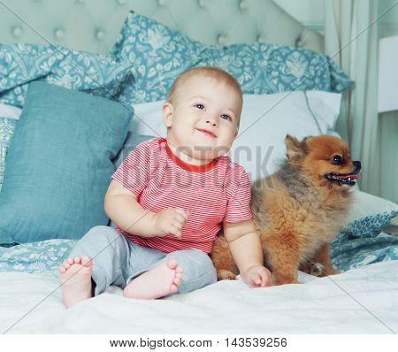 cute baby in the bed at home with his dog