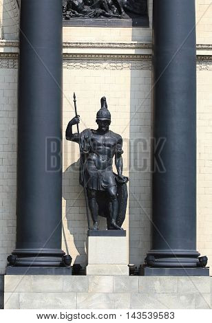 Cast-iron statue of a medieval warrior in armor located between columns of the monumental structure