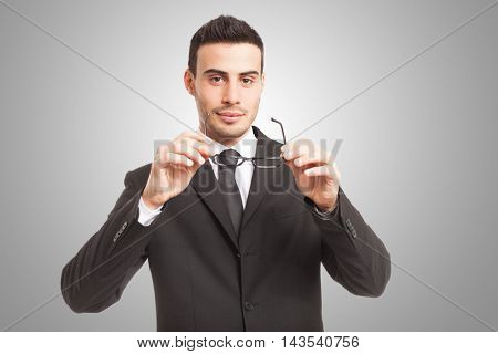 Portrait of an handsome smiling businessman holding his glasses