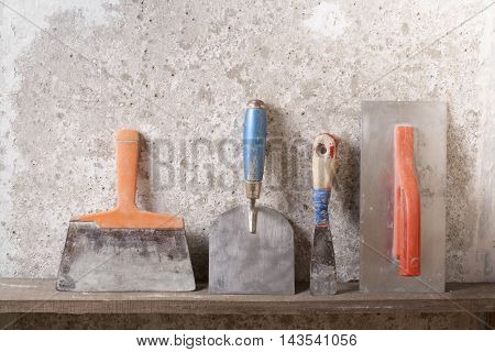 Construction tools on concrete background. Copy space for text. Set of assorted plaster trowel tools and spatula .