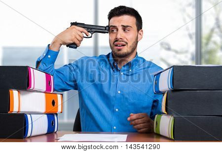 Businessman with black metal gun near temple head in his office