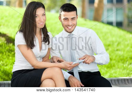 Businesspeople using a tablet outdoor