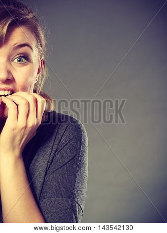 Frustration mental disorder psychology fear stress concept. Nervous girl biting nails. Stressed young blonde lady chewing off her fingers.