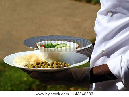 Appetizer in a white plate in the hands of the cook