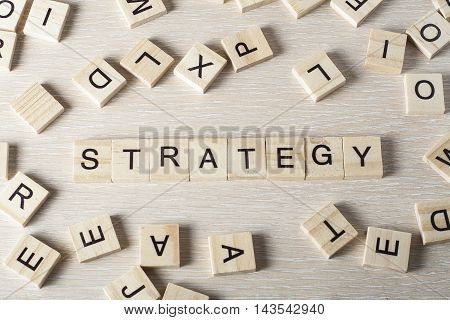 Strategy word written on wood block. Wooden abc.