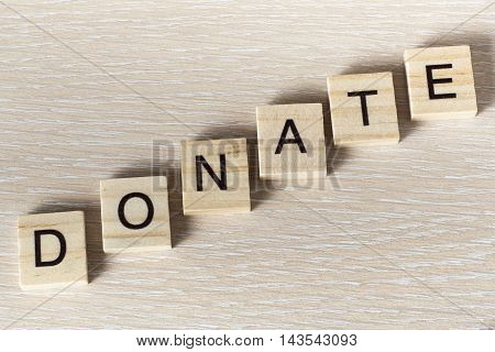 text of DONATE on cubes. Wooden abc.
