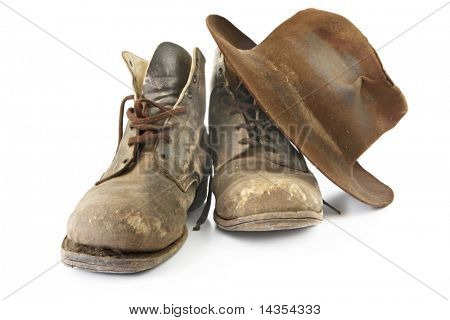 Battered old work boots and felt hat, isolated on white.  Used continuously since the 1940's!