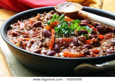 A pan of chilli, ready to serve.  Soft focus, shallow depth of field.