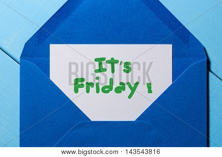 The words It's Friday written on a peace of paper in blue envelope. Happy week concept.