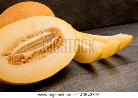 Fresh sliced melon half and three pieces on the black background