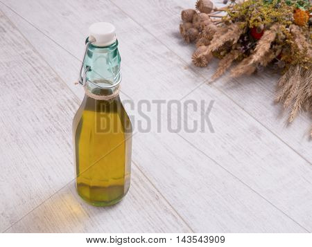 Glass bottle of sunflower oil and wild flowers poppy and herbs on the white table