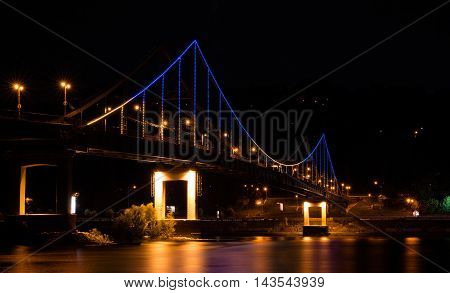 Pedestrian bridge illuminated in the night. Kiev Ukraine. The lights are very symbolic they depict national blue and yellow flag.