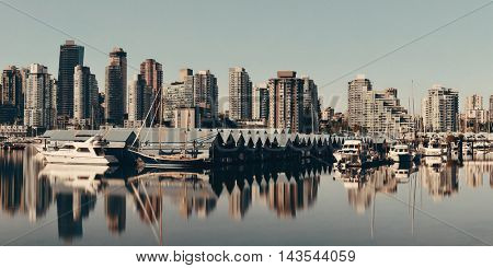 Vancouver downtown with urban buildings and boat with water reflections