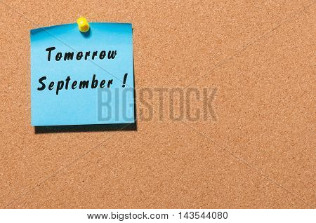 Tomorrow September written on a sticker at notice board with empty space for text.