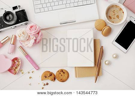 workspace with notebook keyboard, photo camera, open notebook, sketchbook and coffee on white background. Flat lay, top view office table desk.