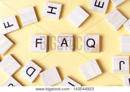 FAQ word written on wood block. Wooden ABC.