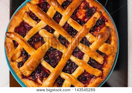 Cherry pie with lattice top on fall themed napkin and mini pumpkins.