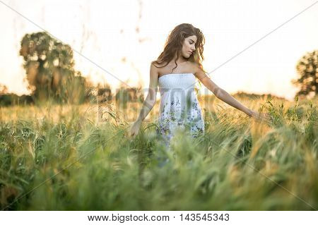 Pretty girl stands in the rye field and looks at the left hand on the sunset background. Woman touches the rye. She wears a light dress with prints of flowers. Outdoors. Horizontal.