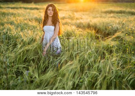 Amazing girl stands in the rye field and looks into the camera on the sunset background. Woman touches the rye. She wears a light dress with prints of flowers. Outdoors. Horizontal.