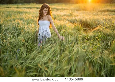 Happy girl stands in the rye field and looks at the left hand on the sunset background. Woman touches the rye. She wears a light dress with prints of flowers. Outdoors. Horizontal.