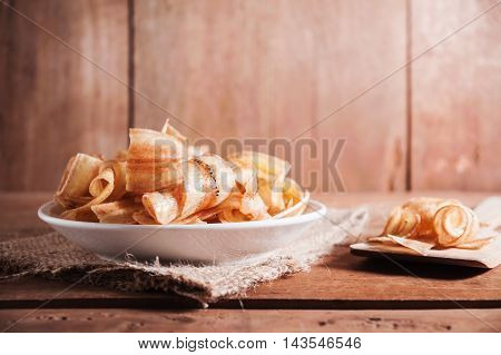 Banana chips in white plate on wooden table still life and dark tone with vintage style