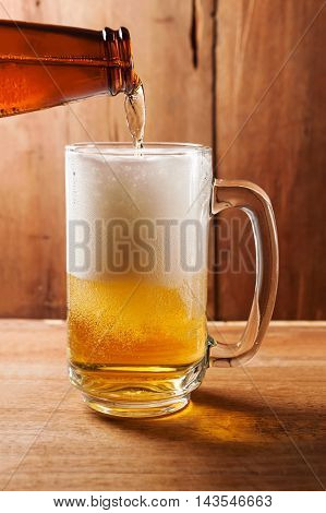 Glass of beer on wooden texture in still life tone